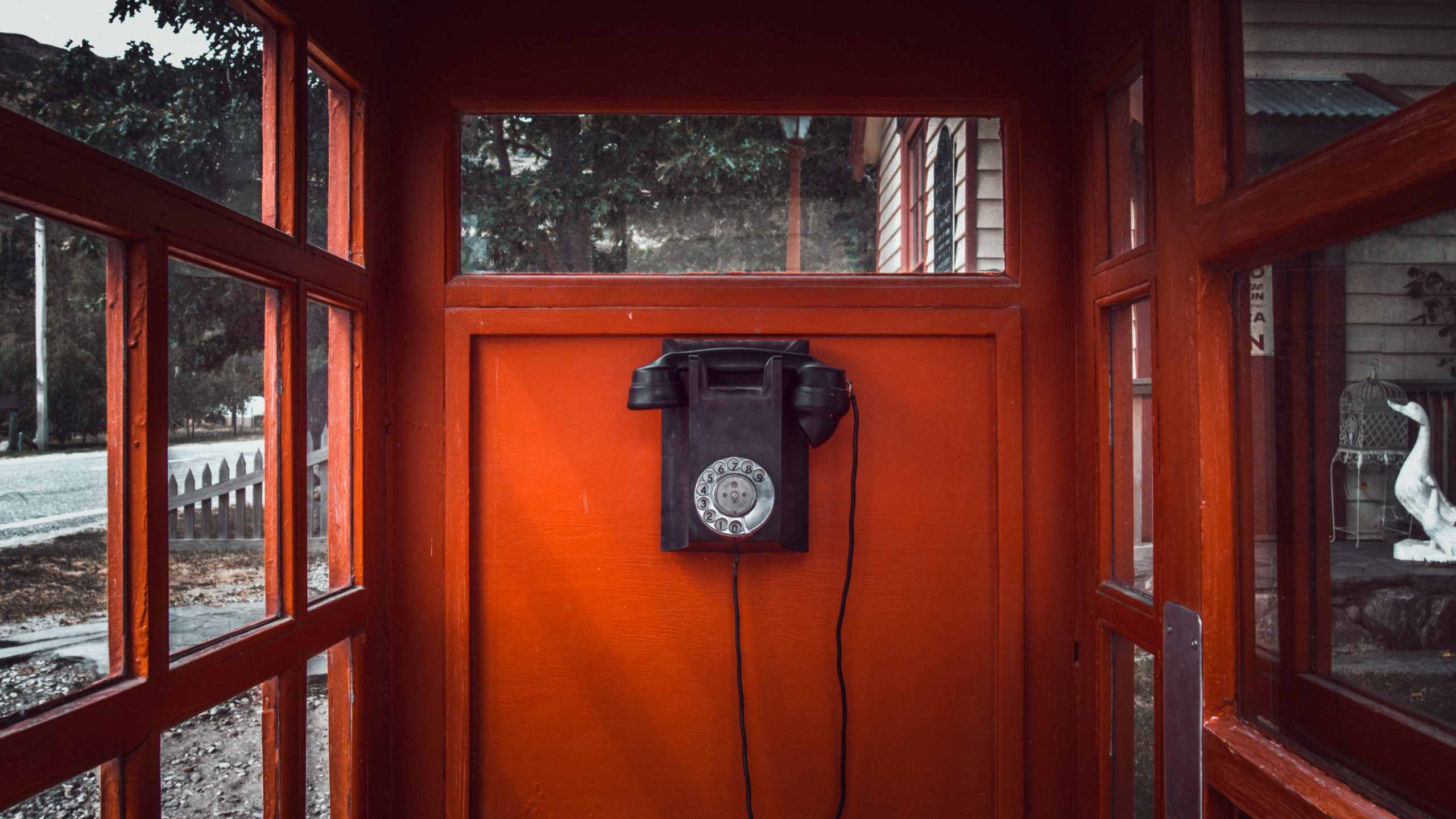 An old red telephone booth with a black dial phone in the center
